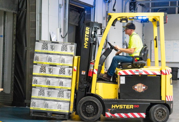 A factory worker moves boxes